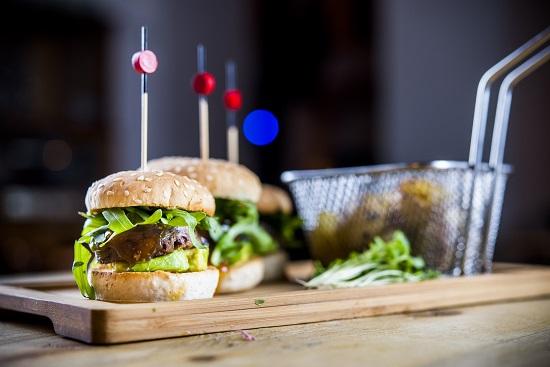 Mini hamburguesas de rabo de toro con aguacate y chutney de mango con patatas al horno.