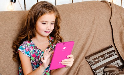 Cute little girl with tablet pc on the sofa at home